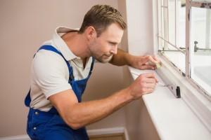 Lucrator de la firma specializata in reparatii termopane care verifica daca fereastra de termopan a fost montata drept