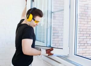 Muncitor de la firma specializata in reparatii termopane care monteaza o fereastra cu geam termopan