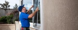 Muncitor de la firma de reparatii termopane care repara o plasa anti-insecte, anti-tantari